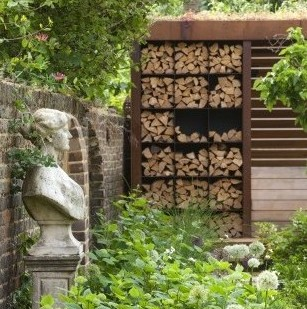 PRIVATE GARDEN LONDON DESIGNED BY LUCY WILLCOX AND ANA SANCHEZ MARTIN: BORDER - ALLIUM MOUNT EVEREST, STATUE, CORTEN STEEL LOG STORE. LOGS, FIRE PIT, BUG HOTEL, WILDLIFE FRIENDLY